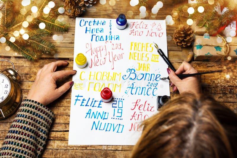 Escritura de una tarjeta de la Feliz Año Nuevo en diversas idiomas fotos de archivo