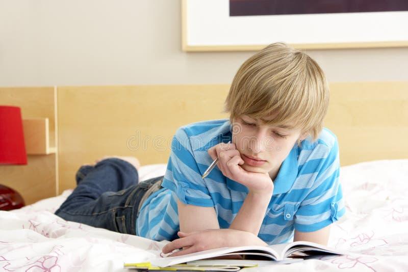 Escritura del adolescente en diario en dormitorio fotografía de archivo