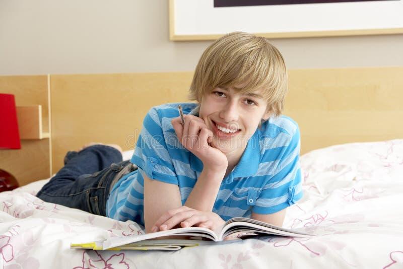 Escritura del adolescente en diario en dormitorio imagen de archivo libre de regalías