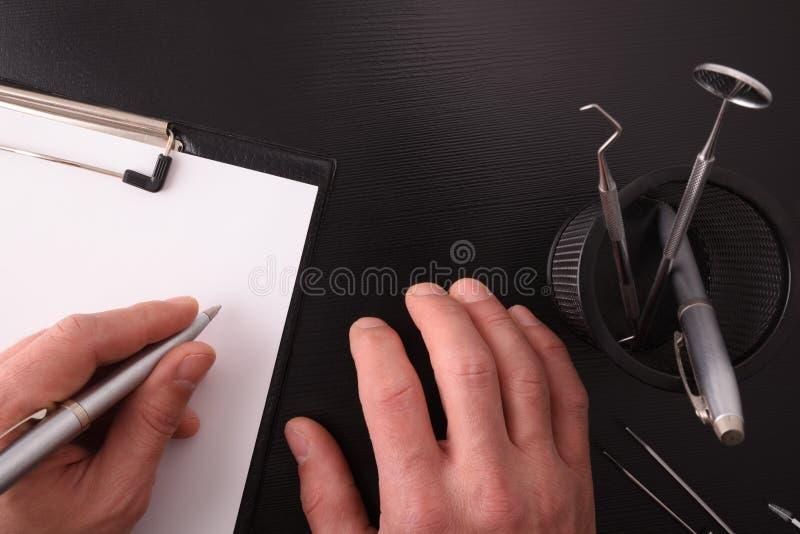 Escritura del doctor del dentista en su opinión de escritorio foto de archivo