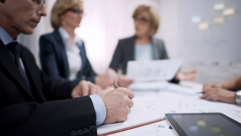 Escritura del encargado de ventas en cuaderno durante la reunión del intercambio de ideas, proceso del funcionamiento fotografía de archivo libre de regalías