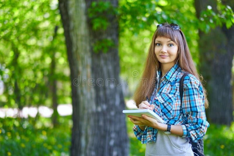 Escritura del estudiante del adolescente en cuaderno en parque Preparación para los exámenes en la universidad o la universidad imágenes de archivo libres de regalías