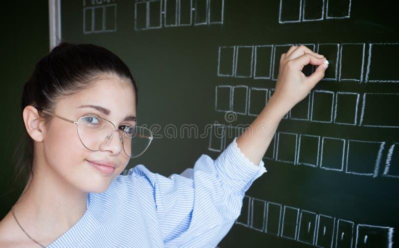 Escritura del estudiante en la pizarra con tiza fotos de archivo libres de regalías