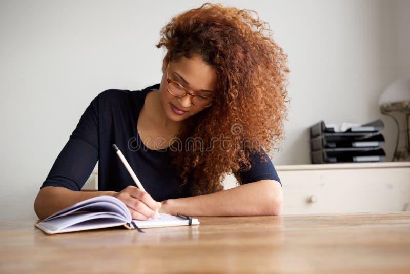 Escritura del estudiante universitario en libro en casa imágenes de archivo libres de regalías
