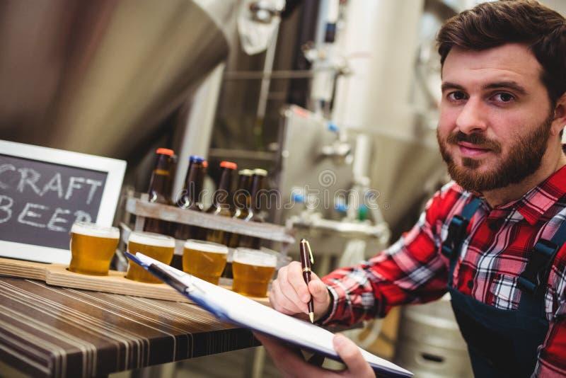 Escritura del fabricante mientras que examina la cerveza en cervecería foto de archivo libre de regalías