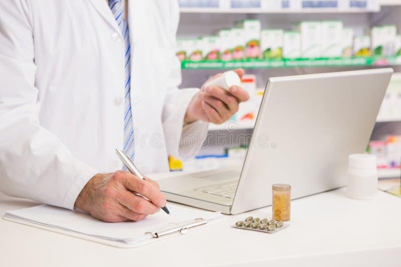 Escritura del farmacéutico en la medicación del tablero y de la tenencia imágenes de archivo libres de regalías