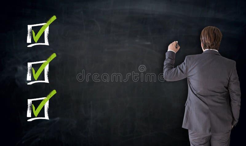 Escritura del hombre de negocios con concepto del checkbox en la pizarra imagen de archivo libre de regalías