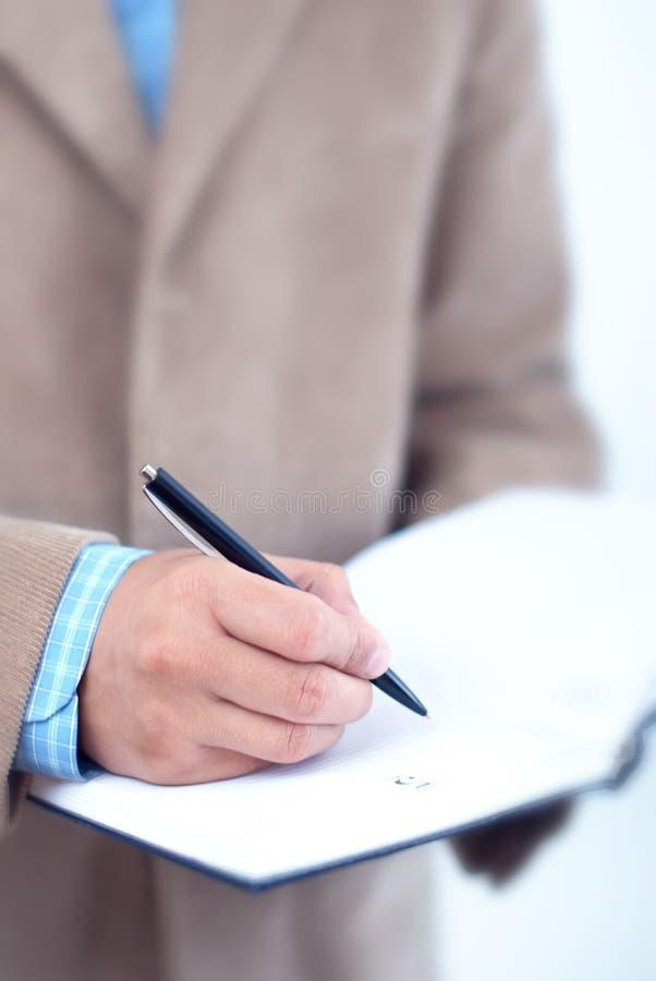 Escritura del hombre de negocios en agenda. foto de archivo