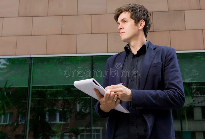 Escritura del hombre de negocios en cuaderno foto de archivo libre de regalías