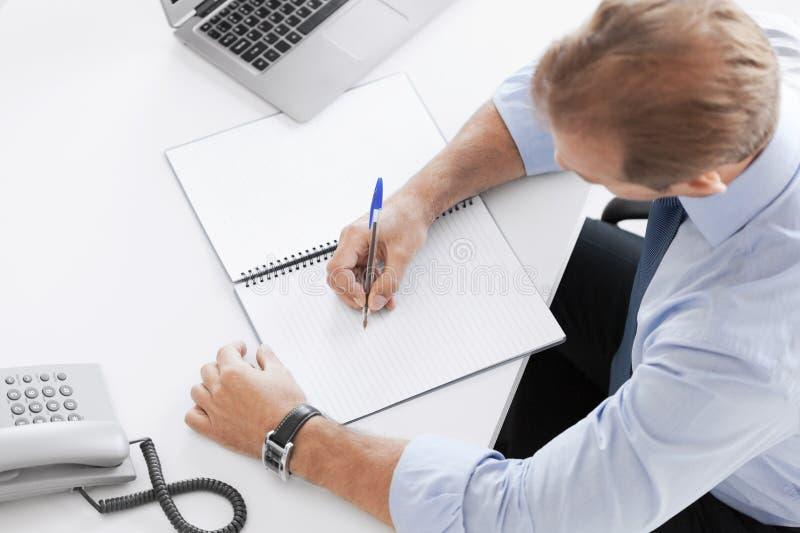 Escritura del hombre de negocios en cuaderno fotografía de archivo libre de regalías