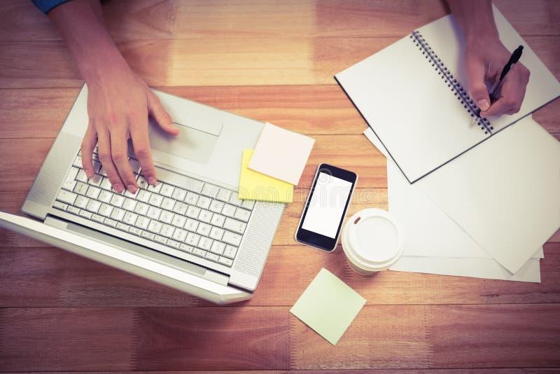 Escritura del hombre de negocios en el libro espiral usando el ordenador portátil foto de archivo
