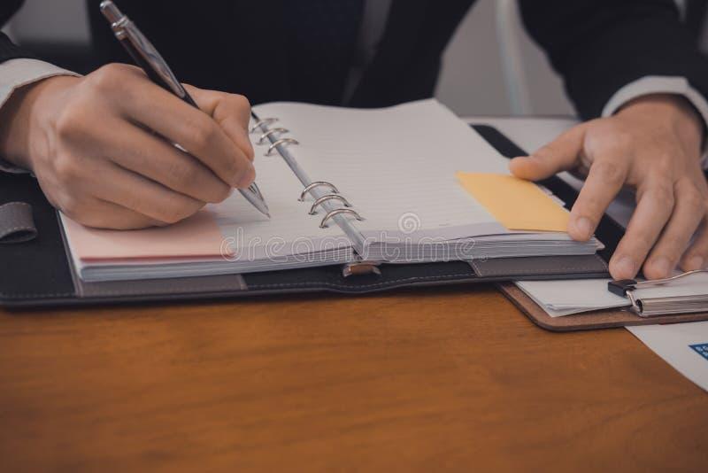 escritura del hombre de negocios en el papel en el lugar de trabajo entreprene masculino joven foto de archivo
