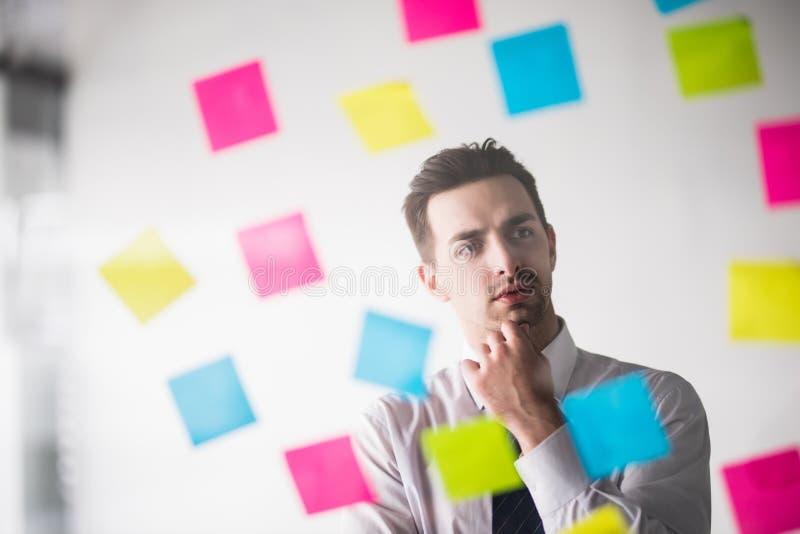 Escritura del hombre de negocios en etiquetas engomadas en la oficina y pensamiento en ellas fotografía de archivo libre de regalías