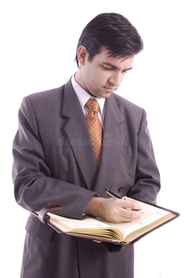 Escritura del hombre de negocios en su agenda fotos de archivo libres de regalías