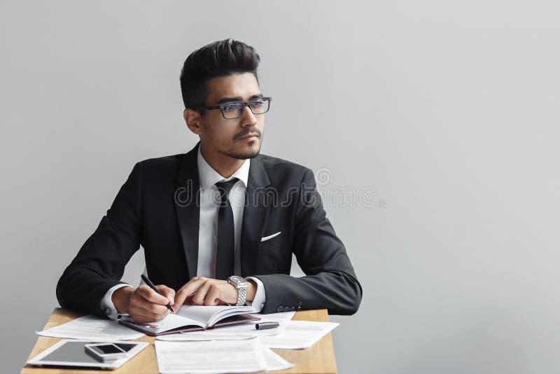 Escritura del hombre de negocios en un cuaderno y miradas lejos de la cámara en un fondo gris fotos de archivo libres de regalías