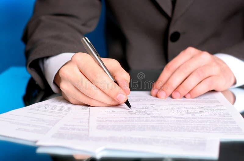 Escritura del hombre de negocios en una forma foto de archivo libre de regalías