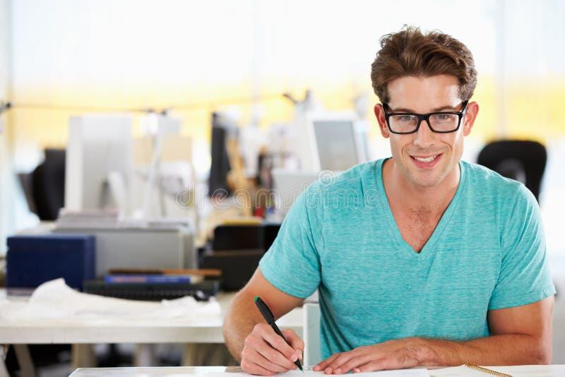Escritura del hombre en el escritorio en oficina creativa ocupada imagenes de archivo