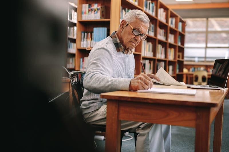 Escritura del hombre mayor que se sienta en una sala de clase de la universidad fotos de archivo libres de regalías