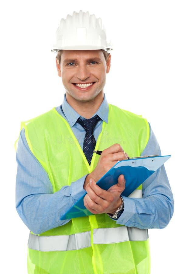 Escritura del ingeniero de construcción en la libreta imagen de archivo libre de regalías
