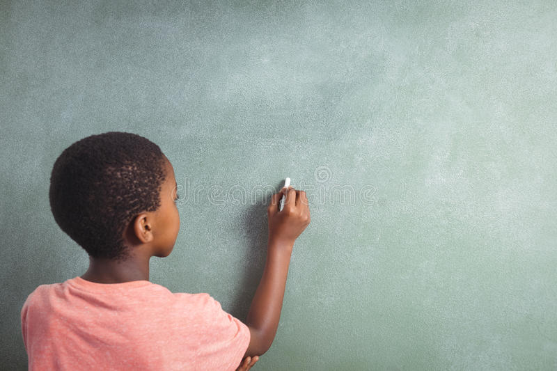 Escritura del muchacho con tiza en greenboard en escuela fotografía de archivo