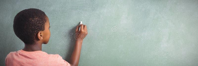 Escritura del muchacho con tiza en greenboard en escuela fotos de archivo