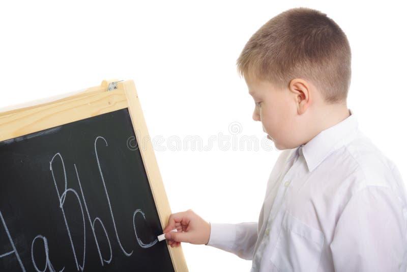 Escritura del muchacho en la pizarra foto de archivo libre de regalías
