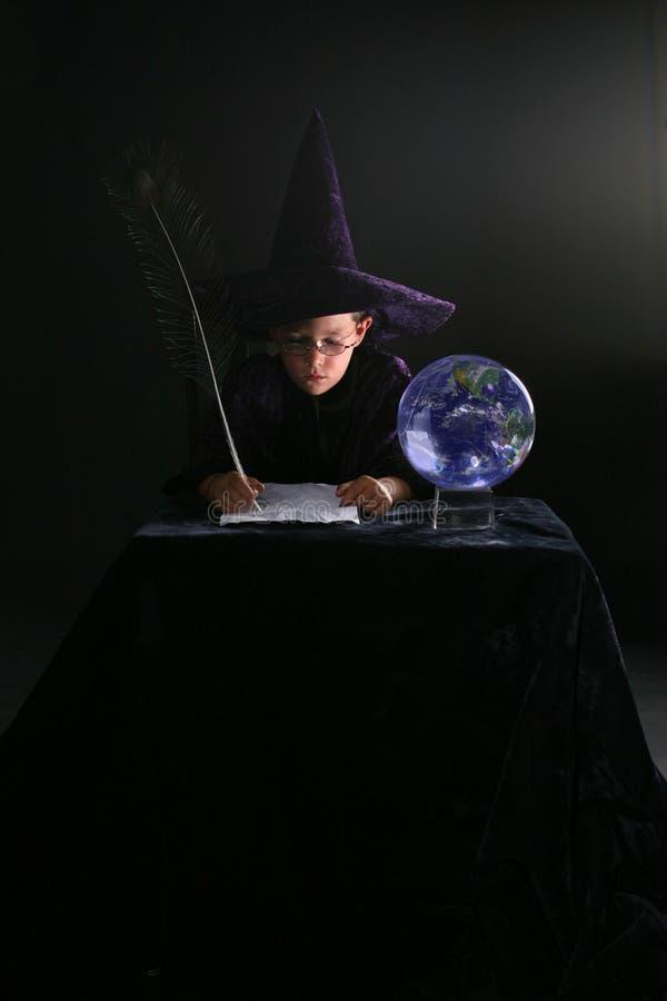Escritura del niño del mago con la canilla de la pluma foto de archivo libre de regalías
