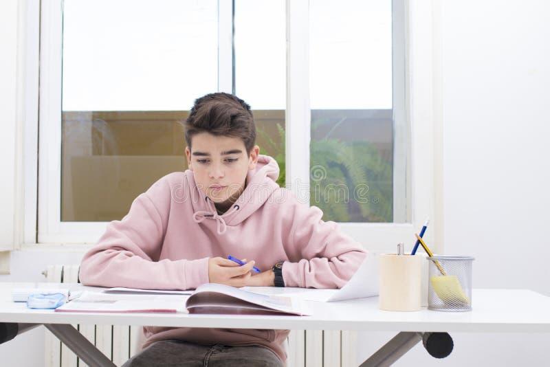 Escritura del niño en el escritorio del hogar o de la escuela fotos de archivo