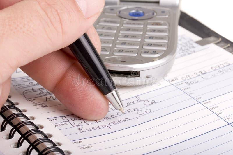 Escritura en agenda con el teléfono celular fotos de archivo libres de regalías