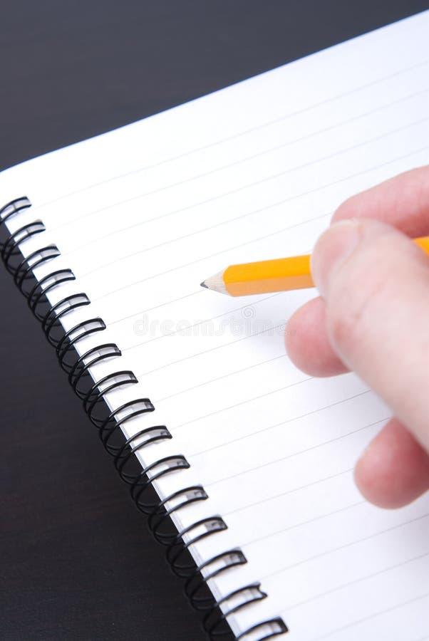 Escritura en un cuaderno espiral en blanco imágenes de archivo libres de regalías