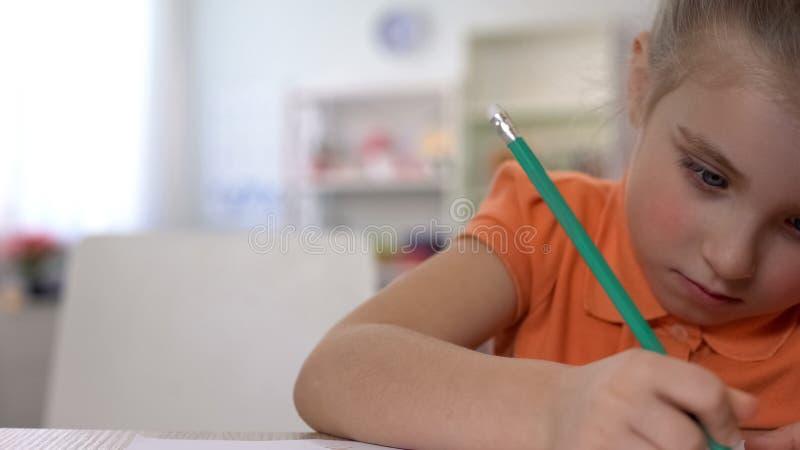 Escritura estudiosa con la tabla del l?piz en casa, educaci?n de la ni?a de la ni?ez imagenes de archivo
