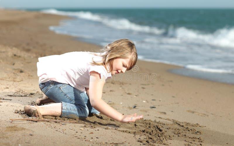 Escritura feliz de la muchacha en la arena imagen de archivo libre de regalías