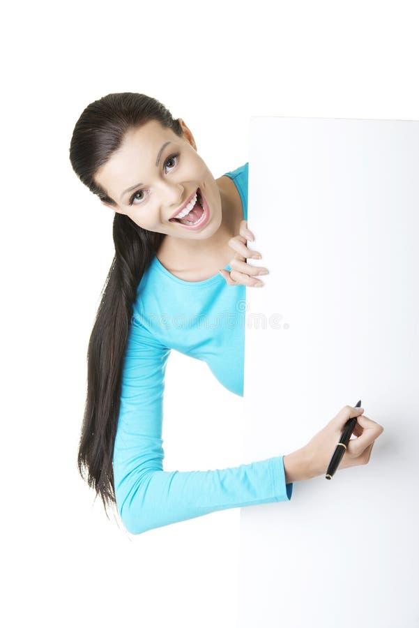 Escritura feliz de la mujer con una pluma en tarjeta en blanco. imagenes de archivo