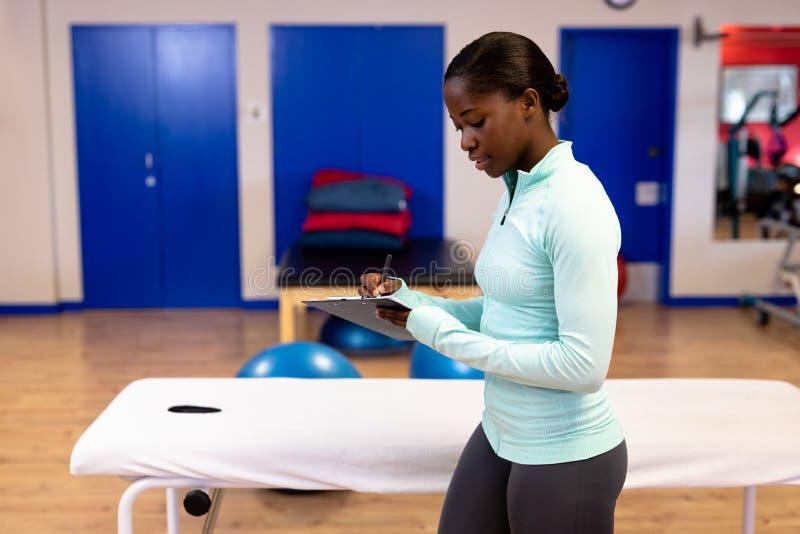 Escritura femenina del instructor en el tablero en centro de deportes foto de archivo libre de regalías