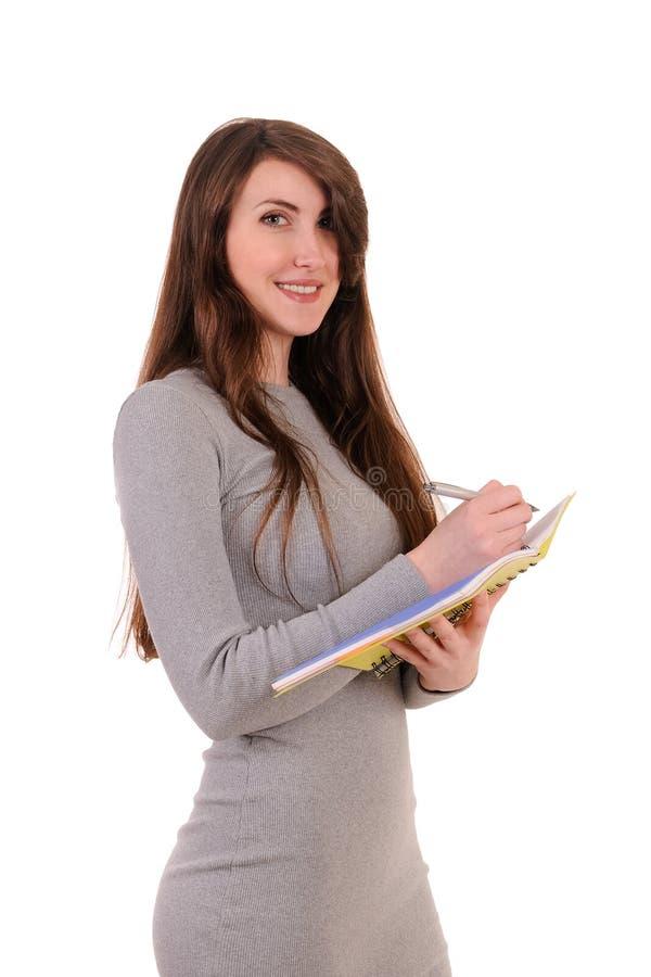 Escritura hermosa bastante joven de la mujer, organizador del cuaderno de la tenencia imagen de archivo
