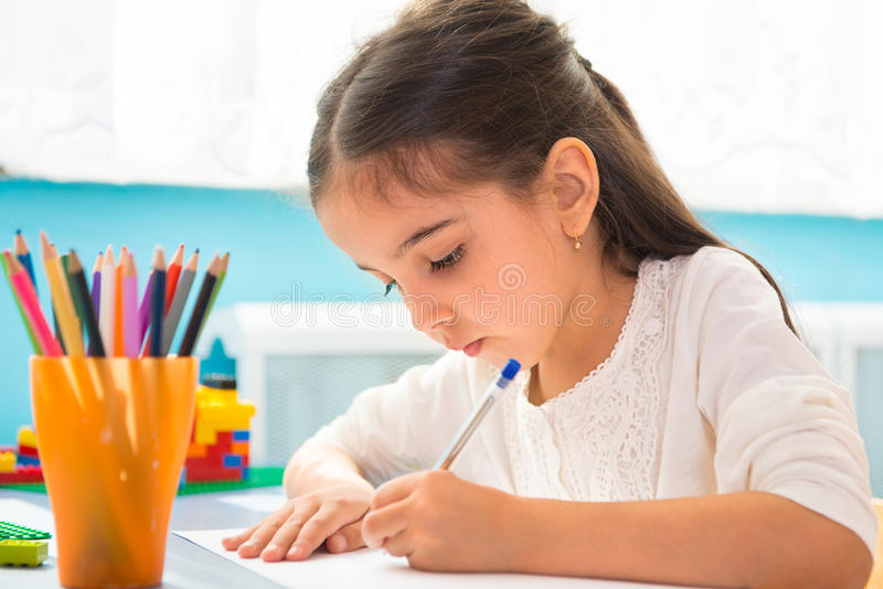 Escritura hispánica linda de la muchacha en la escuela imagen de archivo