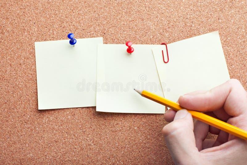 Escritura humana de la mano con el lápiz en los papeles de nota foto de archivo libre de regalías