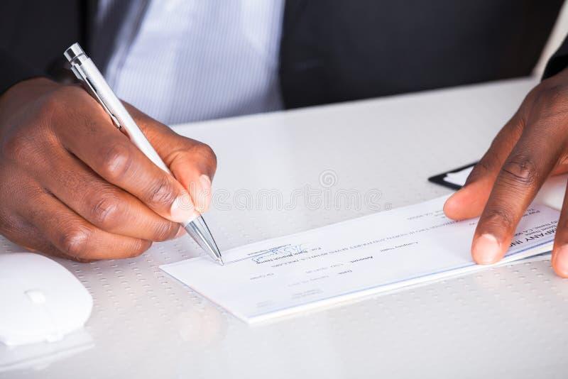 Escritura humana de la mano en el cheque foto de archivo