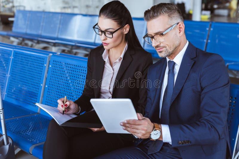 escritura joven de la empresaria en libreta mientras que hombre de negocios que usa la tableta digital fotos de archivo