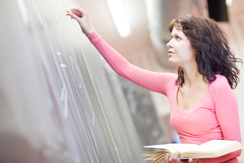 Escritura joven del estudiante universitario en la pizarra foto de archivo libre de regalías