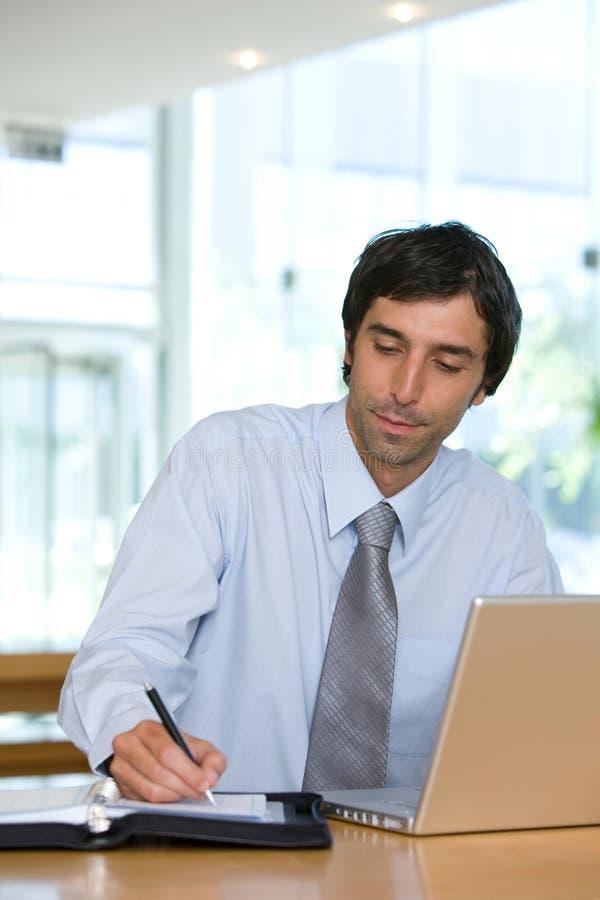 Escritura joven del hombre de negocios en la libreta imagenes de archivo