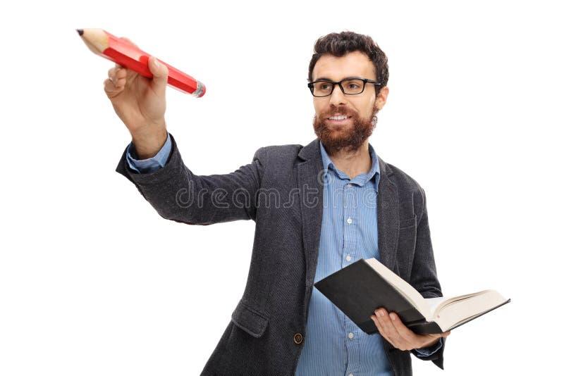 Escritura joven del profesor con un lápiz y una tenencia un libro fotos de archivo