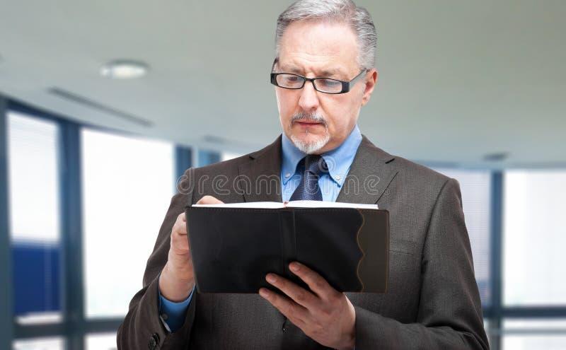 Escritura madura del hombre de negocios en su orden del día fotografía de archivo libre de regalías