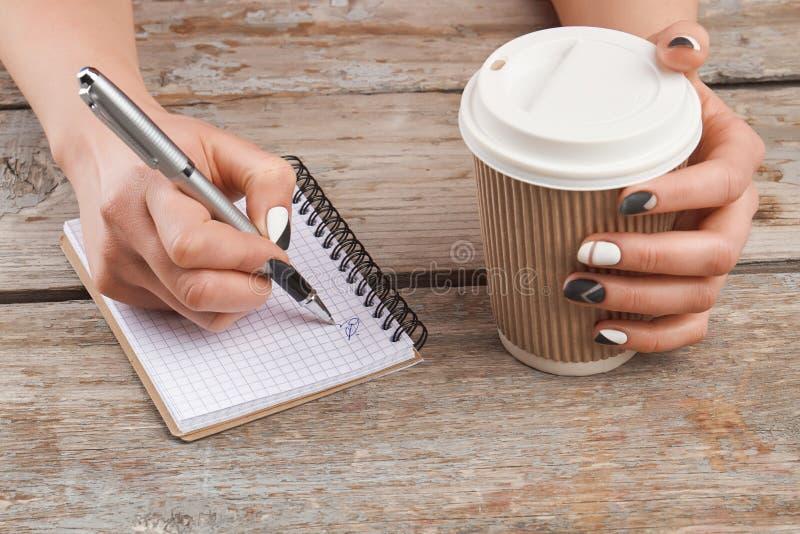 Escritura Manicured de la mano en el cuaderno foto de archivo
