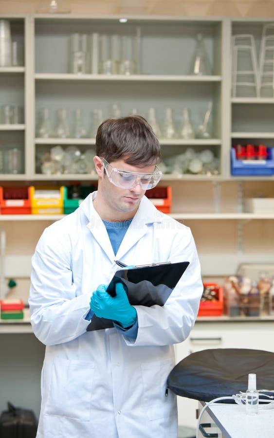 Escritura masculina concentrada del científico en un sujetapapeles foto de archivo