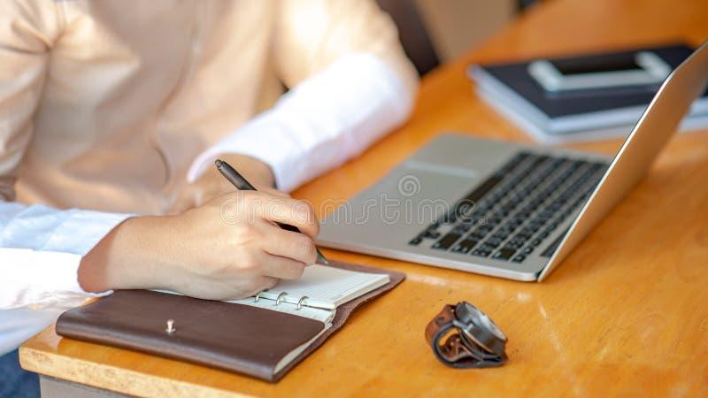 Escritura masculina de la mano en el cuaderno en el escritorio fotografía de archivo