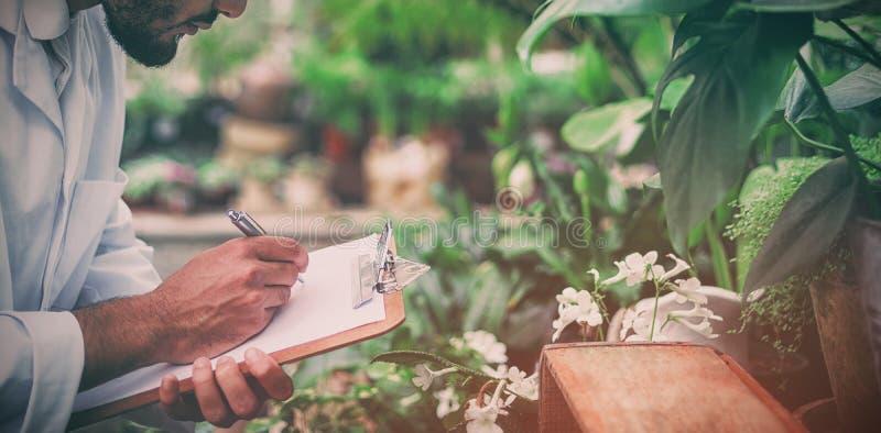 Escritura masculina del científico en tablero mientras que examina las plantas fotografía de archivo