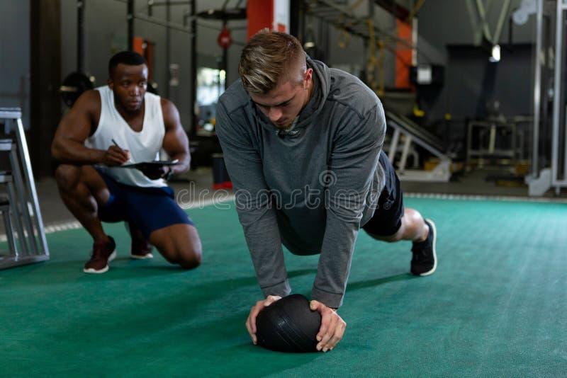 Escritura masculina del instructor en el tablero mientras que ejercicio atlético masculino con la bola del ejercicio fotografía de archivo