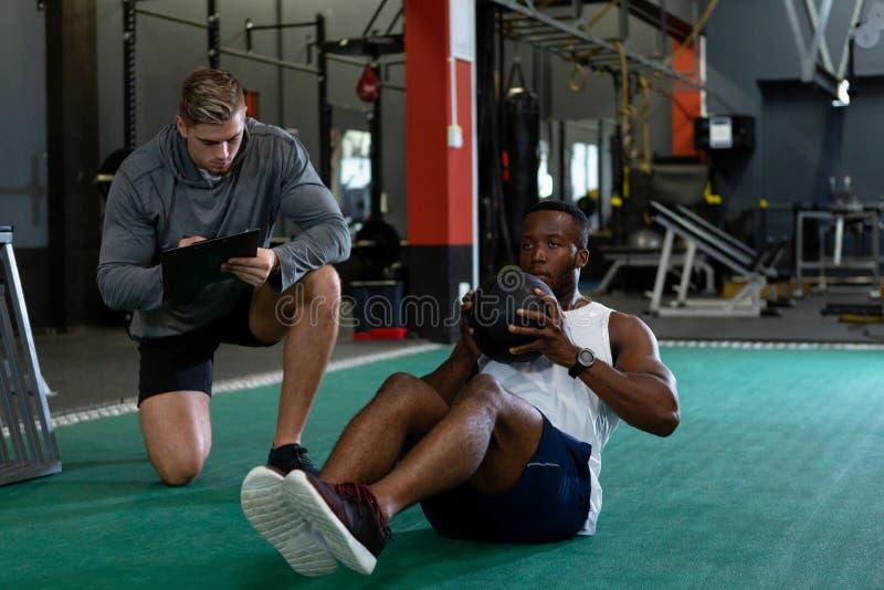Escritura masculina del instructor en el tablero mientras que ejercicio atlético masculino con la bola del ejercicio imagenes de archivo