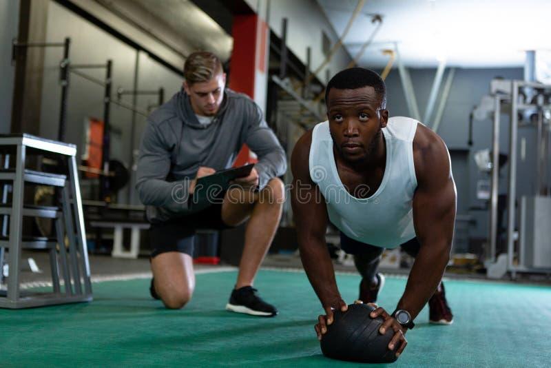 Escritura masculina del instructor en el tablero mientras que ejercicio atlético masculino con la bola del ejercicio fotografía de archivo libre de regalías